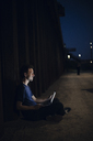 Mid adult man sitting cross-legged on ground, using laptop at night - GUSF00984