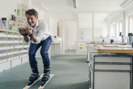 Businessman skiing in office - GUSF01011
