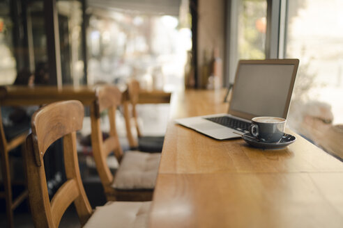 Laptop with blank screen in coffee shop - GUSF01014