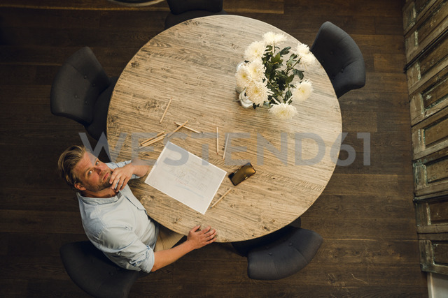 Mature man sitting at a round table, drawing with coloured pencils, overhead view - GUSF01023