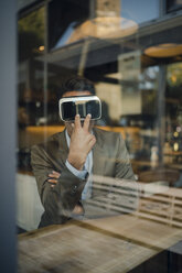 Mature businessman sitting in coffee shop, looking through VR glasses - GUSF01032