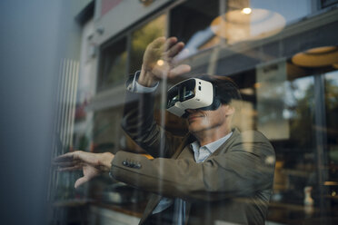 Mature businessman sitting in coffee shop, looking through VR glasses - GUSF01035