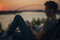 Man using smartphone at sunset - GUSF01047