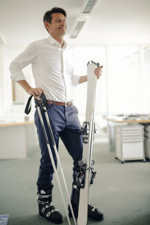 Businessman skiing in office - GUSF01083
