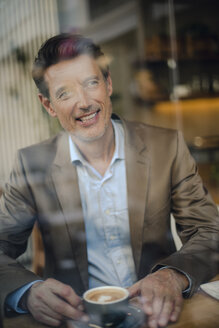 Mature businessman sitting in coffee shop, smiling - GUSF01110