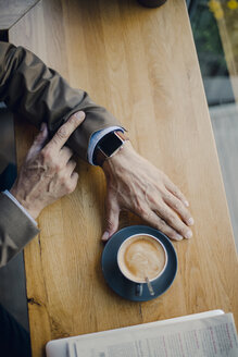 Mature businessman sitting in coffee shop, checking time - GUSF01116