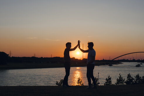 two friends high-fiving at sunset, standing by the river - GUSF01122