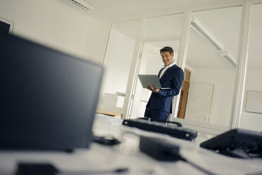 Businessman standing in office, using laptop - GUSF01143