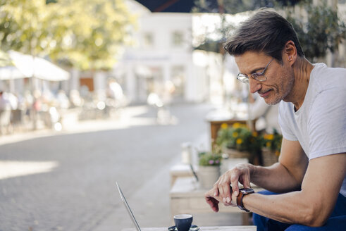 Mature businessman sitting in coffee shop, checking time - GUSF01152
