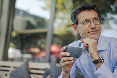Mature businessman sitting in coffee shop, drinking coffee - GUSF01158