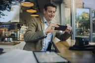 Mature businessman sitting in coffee shop, using smartphone - GUSF01173