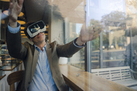 Mature businessman sitting in coffee shop, looking through VR glasses, dancing - GUSF01176