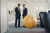 Two businessman checking smartphone with yellow fitness  ball in foreground - GUSF01194