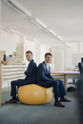 Two businessman checking smartphone with yellow fitness  ball in foreground - GUSF01197