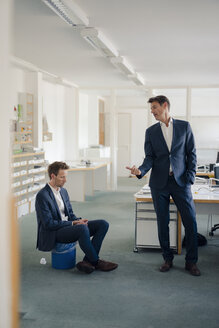 Manager making colleague, sitting on wastepaper basket, redundant - GUSF01200