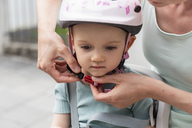 Mother and daughter, daughter wearing helmet sitting in children's seat - DIGF04956