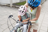 Mother and daughter riding bicycle, daughter wearing helmet sitting in children's seat, fastening seat belt - DIGF04959