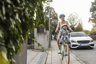Mother and daughter riding bicycle, daughter wearing helmet sitting in children's seat - DIGF04962
