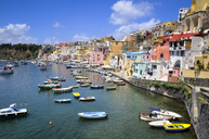 Harbor with moored boats, and colourful waterfront buildings on the hillside overlooking the waterfront. Procida, in the Flegrean Islands off the coast of Naples. - MINF08627