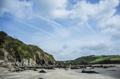 View along the coastline and a sandy beach in a bay, with fields and forest sloping down to the beach. - MINF08664