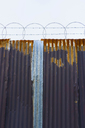 Worn corrugated metal fence, razor wire above. - MINF08679