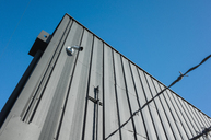 Low angle view of building exterior with surveillance camera, barbed wire in foreground. - MINF08685