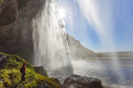 Person standing on the edge of rock near a waterfall cascade over a sheer cliff. - MINF08734