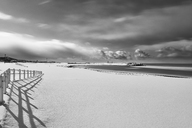 Fence running along a snow-covered beach near the ocean in winter. - MINF08761