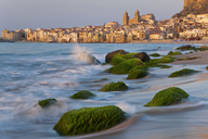 View along coastline with sandy beach, rocks covered in green algae, city in the distance. - MINF08896