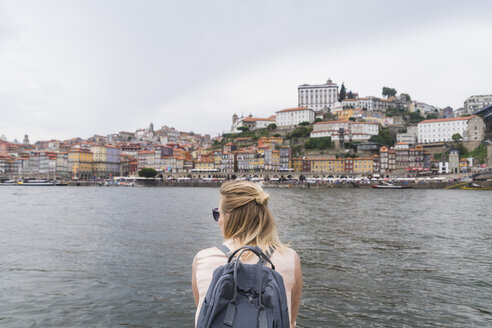 Portugal, Porto, back view of woman with backpack in front of douro River - CHPF00514