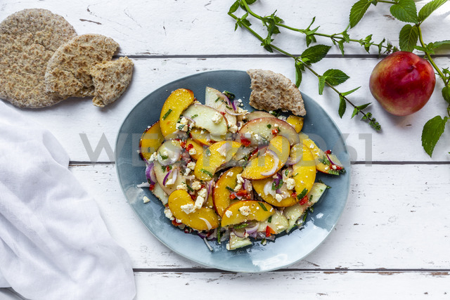 Peach mint feta salad with pita bread on plate, white wood - SARF03920