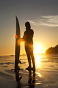 Man stands with surfboard at sunset in British Columbia. - AURF00862