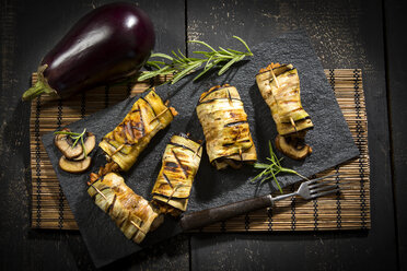 Grilled aubergine slices stuffed with mincemeat, champignons and goat cheese on slate - MAEF12714