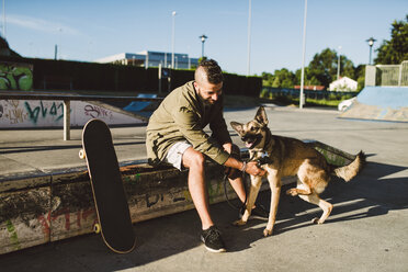 Young man playing with his dog in a skatepark - RAEF02109