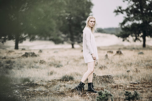 Netherlands, Drents-Friese Wold National Park, young blond woman wearing boots and oversized pullover - JESF00077