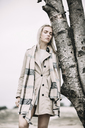 Portrait of fashionable young woman wearing coat and scarf leaning against tree trunk - JESF00080