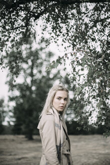 Portrait of fashionable young woman wearing coat and scarf in nature - JESF00083