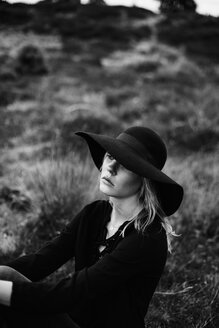 Portrait of young woman wearing black hat sitting on a meadow - JESF00092