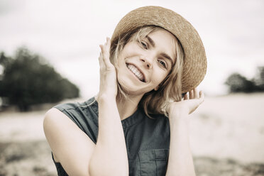 Portrait of smiling young woman wearing straw hat - JESF00110