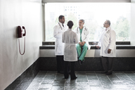Mixed race doctors conferring in a hospital hallway. - MINF08947