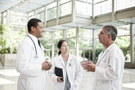 Mixed race group of doctors meeting in lobby of large hospital - MINF08950