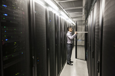 Hispanic man technician doing diagnostic tests on computer servers in a large server farm. - MINF08959