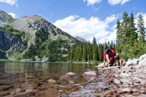 A mother and her 14 month old son play on the shore of Snowmass Lake (10,980ft) on August 10, 2009 in the Maroon Bells in the Snowmass Wilderness just outside of Aspen, Colorado. - AURF01184
