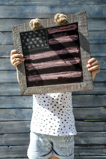 Little girl holding wooden frame with US-American flag - DEGF00957
