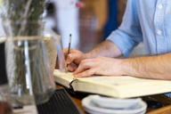 Close-up of man writing in notebook - AFVF01445