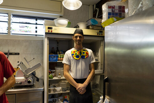Portrait of funny pizza baker wearing clown's bow tie in kitchen - AFVF01460