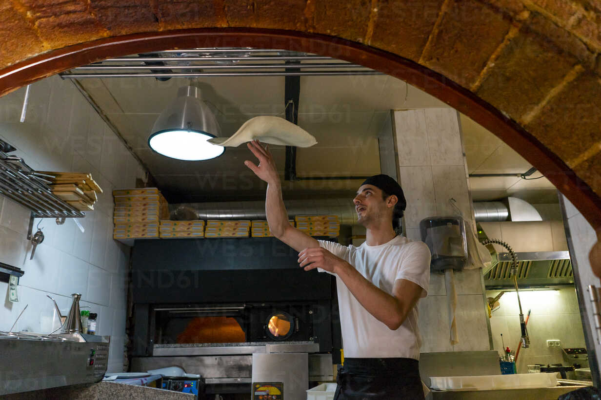 Pizza Baker Preparing Pizza In Kitchen Throwing Dough In The Air Stockphoto