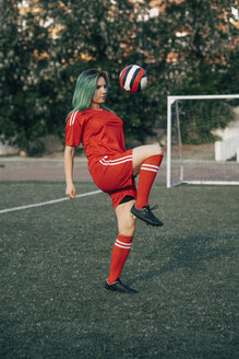 Young woman playing football on football ground balancing the ball - VPIF00508