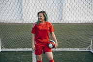 Smiling young woman standing on football ground holding the ball - VPIF00511
