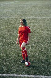 Young woman standing on football ground with the ball - VPIF00514